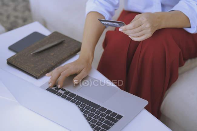Vista parziale della donna a tavola in possesso di carta di credito e utilizzando il computer portatile — Foto stock