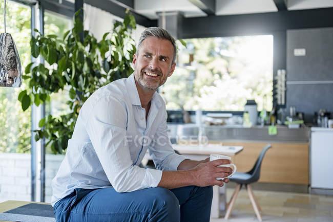 Sorridente uomo maturo a casa seduto sul tavolo con una tazza di caffè — Foto stock