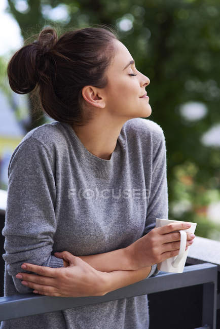 Dreaming beautiful caucasian woman with closed eyes and coffee cup in morning on balcony — Fotografia de Stock