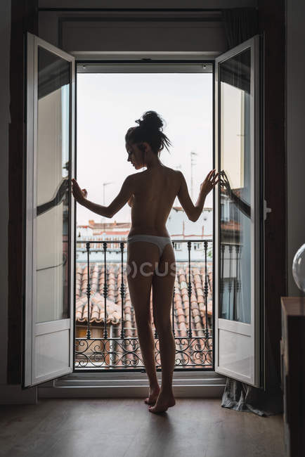 Attractive shirtless young woman standing at balcony door — Stock Photo