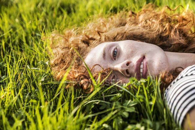 Portrait de jeune femme rousse couchée sur l'herbe verte — Photo de stock