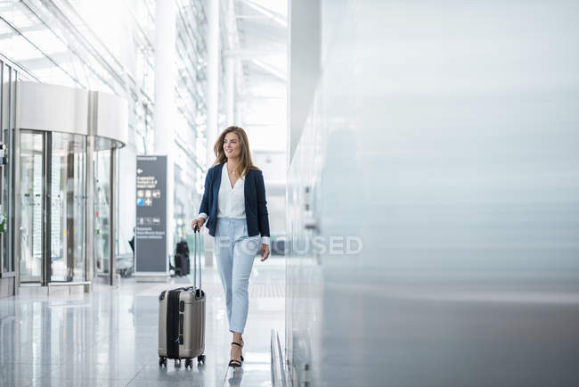 Young businesswoman walking with luggage at the airport — Stock Photo