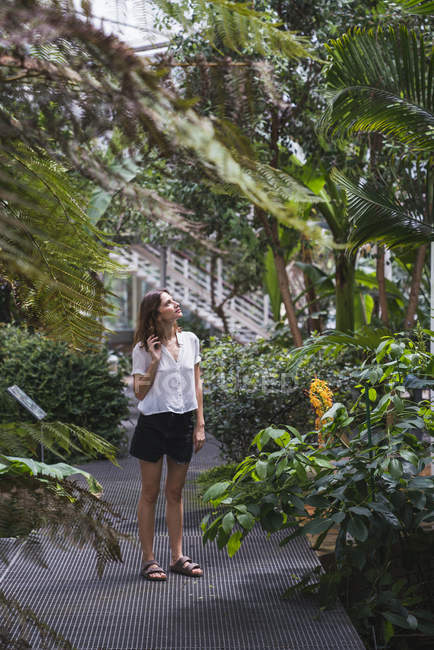 Молодая женщина смотрит на деревья в оранжерее — стоковое фото