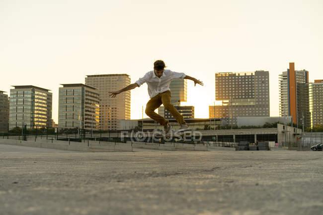 Jeune homme faisant un tour de planche à roulettes dans la ville au coucher du soleil — Photo de stock