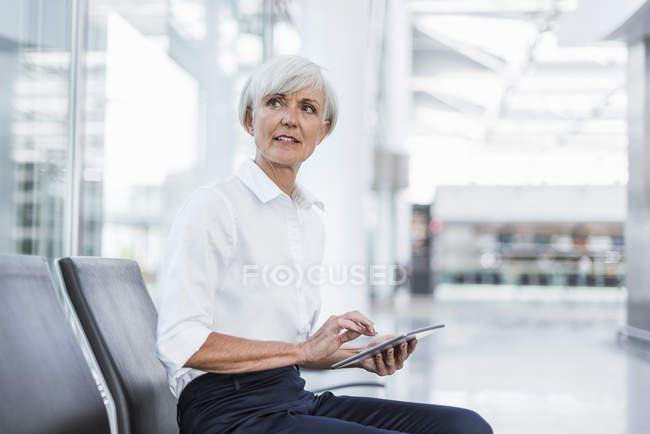 Senior businesswoman sitting in waiting area with tablet and looking around — Stock Photo