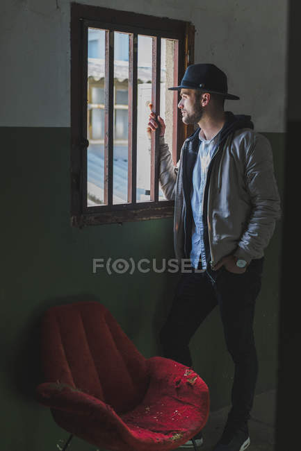 Bearded man wearing black hat, looking out of window — Stock Photo