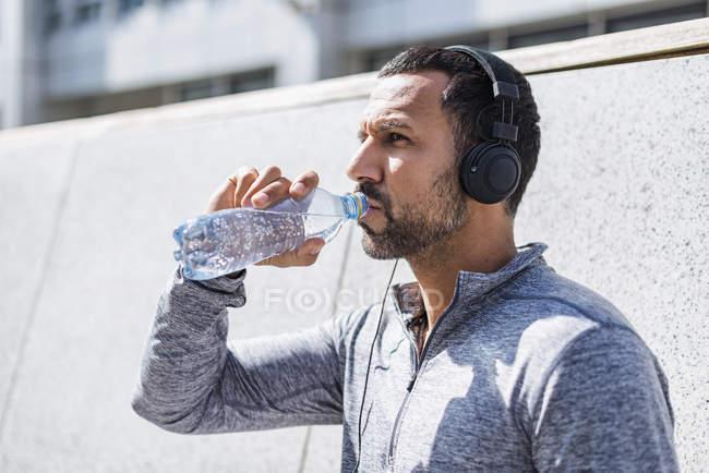 Homem fazendo uma pausa do exercício usando fones de ouvido e bebendo de garrafa — Fotografia de Stock