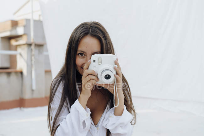 Portrait of young woman taking photo with camera on roof terrace — Stock Photo