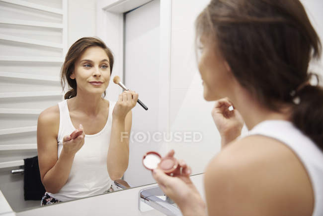 Mirror image of smiling young woman applying makeup in bathroom — Stock Photo