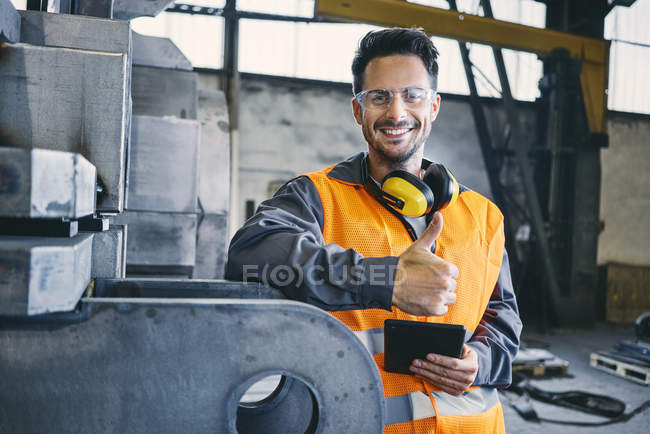 Portrait of smiling man wearing protective workwear showing thumbs up in factory — Stock Photo