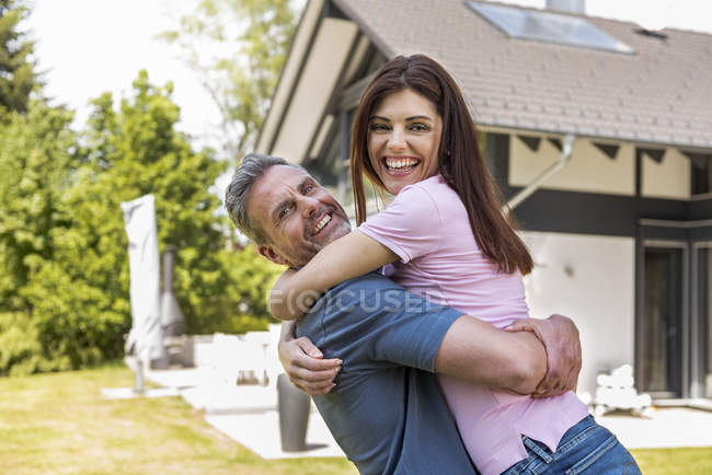 Portrait of happy couple in garden of their home — Stock Photo