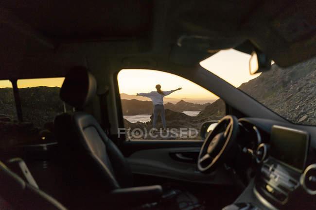 Молодая женщина наслаждается закатом на пляже, вид через автомобиль — стоковое фото