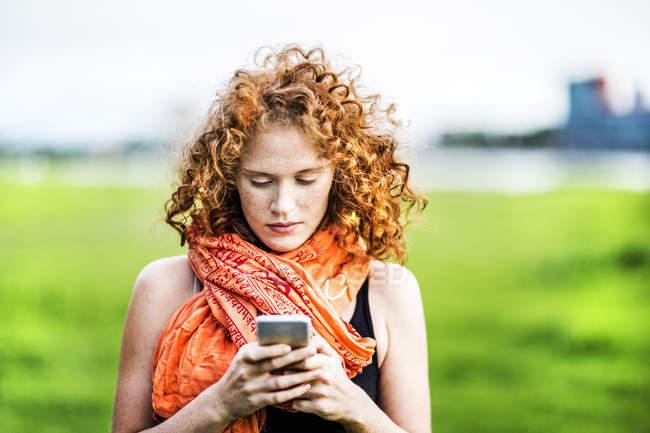 Portrait de jeune femme aux cheveux roux bouclés utilisant un téléphone portable à l'extérieur — Photo de stock
