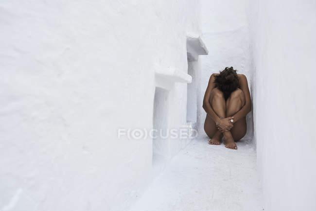 Молодая женщина корточках в стене нишу — стоковое фото