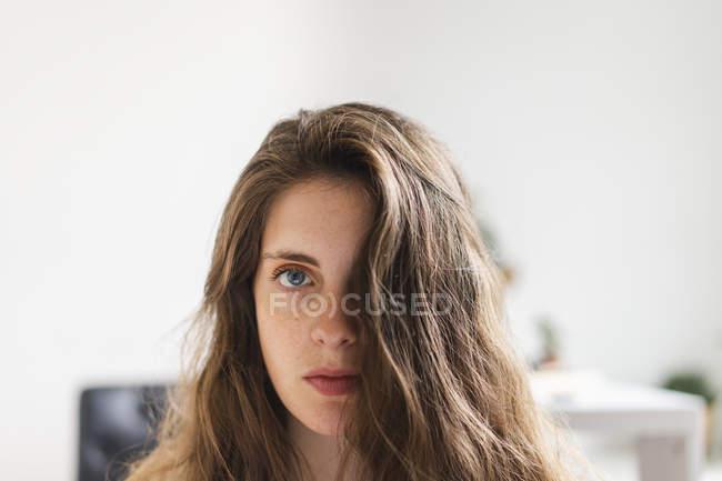 Портрет мыслящей женщины с темными длинными волосами, смотрящей в камеру — стоковое фото
