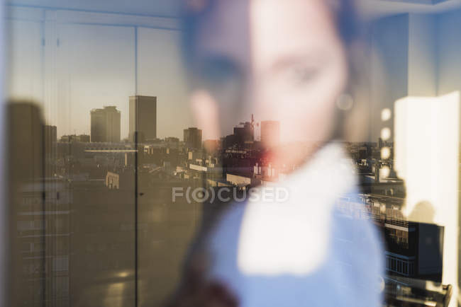 Spain, Madrid, blurred view of woman behind windowpane with reflection of city — Stock Photo