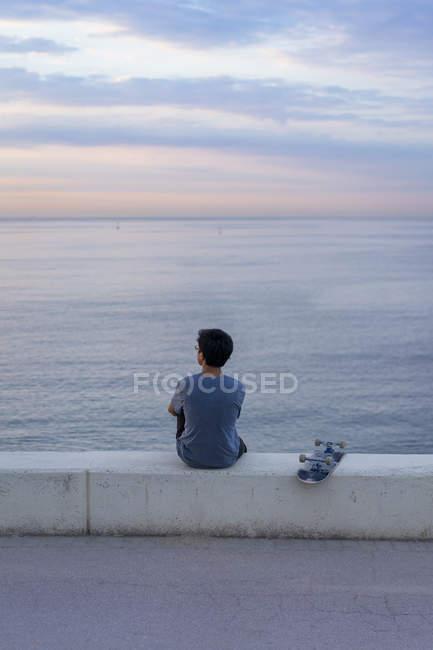 Jovem chinês com skate sentado na parede na praia — Fotografia de Stock