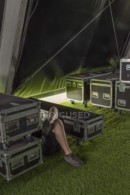 Hombre descansando entre bastidores entre cajas - foto de stock