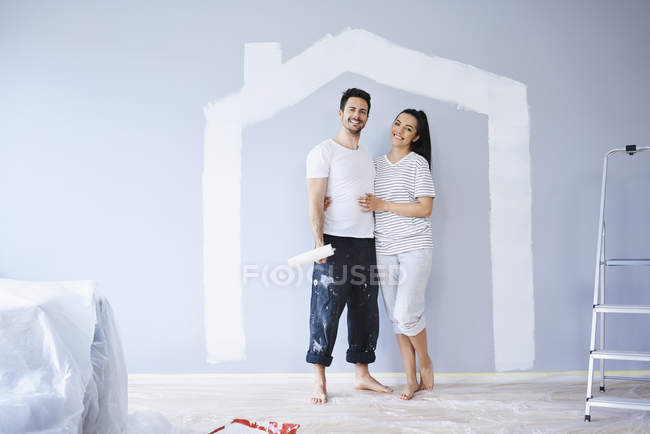 Portrait of happy couple painting in new apartment with house shape on wall — Stock Photo