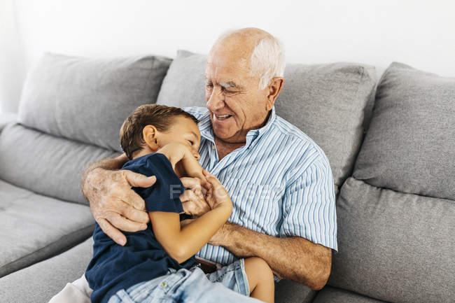 Nieto y abuelo riendo mientras se hacen cosquillas en el sofá - foto de stock