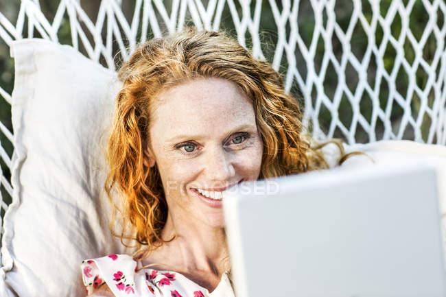 Mulher sorridente deitada na rede com tablet — Fotografia de Stock