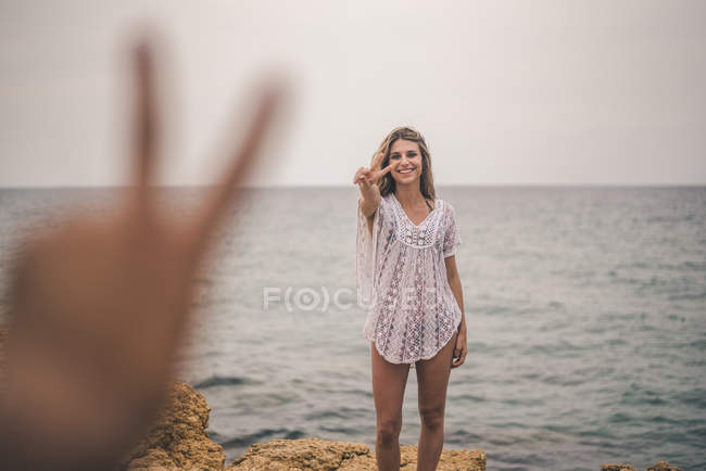 Portrait of happy young woman standing on a rock at the sea making peace sign — Stock Photo