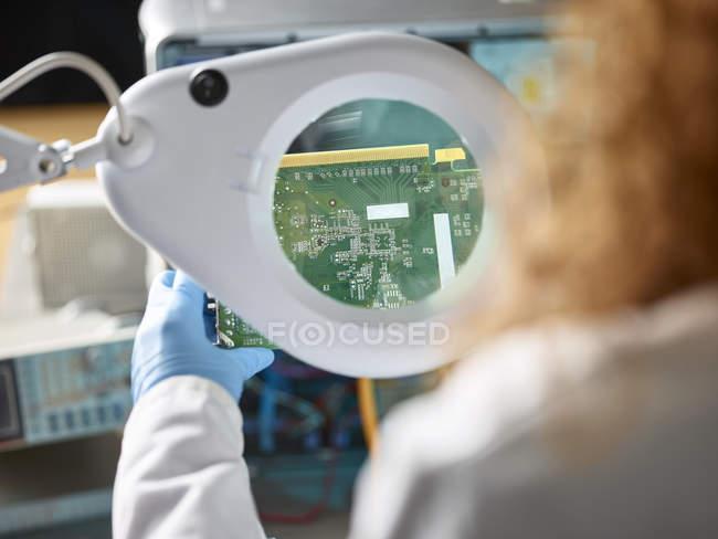 Técnico fêmea que verific a placa de circuito com Magnifier — Fotografia de Stock