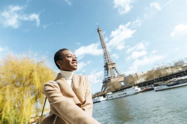 Francia, París, Mujer sonriente en el río Sena con la Torre Eiffel de fondo - foto de stock