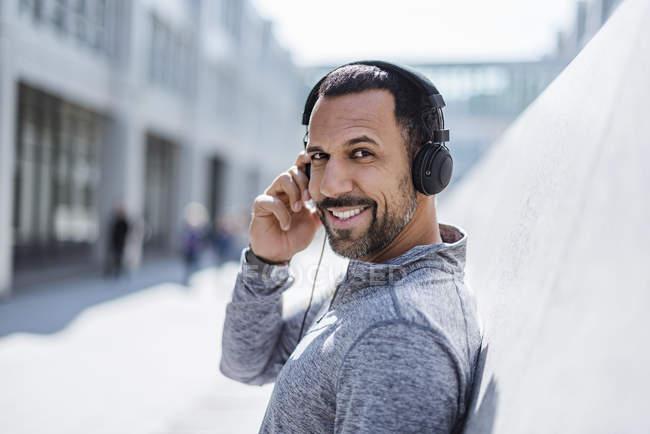 Portrait of smiling man having a break from exercising wearing headphones — Stock Photo