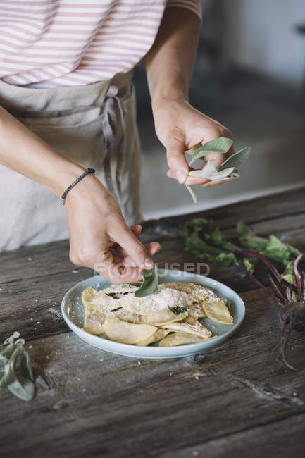 Filled ravioli on plate, sage — Stock Photo