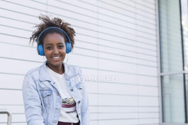 Verticale de jeune femme de sourire écoutant la musique dans le casque bleu et regardant l'appareil-photo — Photo de stock
