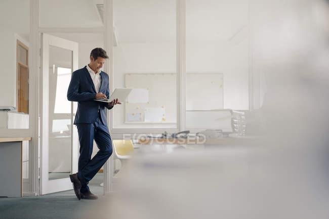 Geschäftsmann steht im Büro und benutzt Laptop — Stockfoto