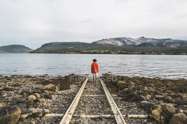 Northern Norway, Man standing alone at fjord, looking at view with lake and mountains — Stock Photo