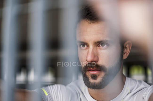 Portrait of confident athlete behind grid — Stock Photo