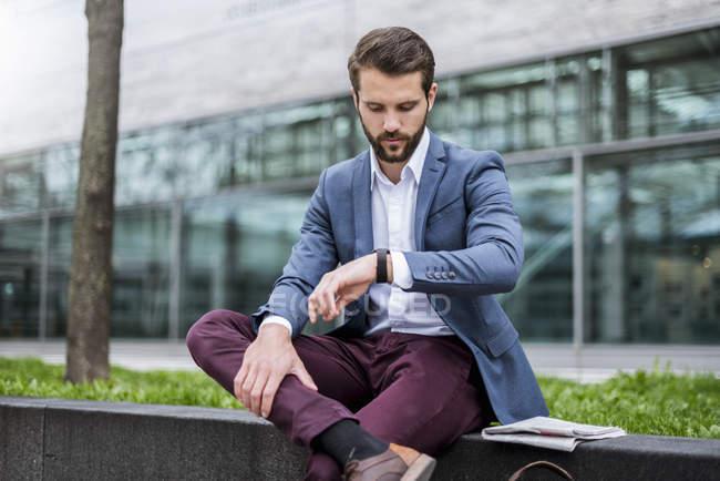 Giovane uomo d'affari seduto all'aperto a controllare l'ora — Foto stock