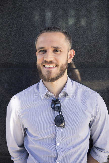 Verticale d'homme d'affaires occasionnel de sourire restant contre le mur — Photo de stock