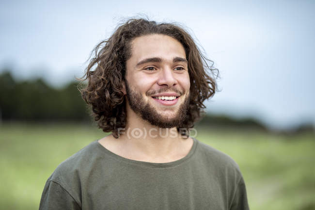 Portrait of happy young man looking away outdoors — Stock Photo