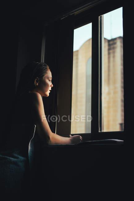 Девочка-подросток, глядя в окно — стоковое фото