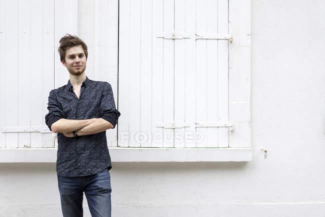 Porträt eines selbstbewussten jungen Mannes, der vor einem Gebäude steht — Stockfoto