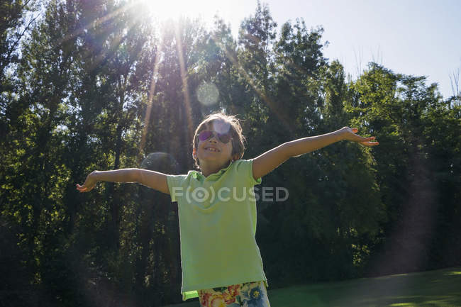 Little girl under rays of sun in garden — Stock Photo