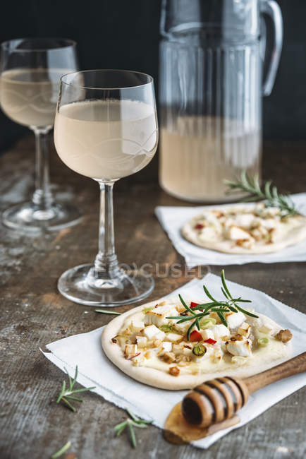 Tarte Flambee with apple, goat cheese, spring onions, rosmary and walnuts and Federweisser — Stock Photo