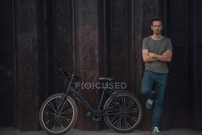 Homem inclinado parede de metal aginsta com braços cruzados por bicicleta — Fotografia de Stock