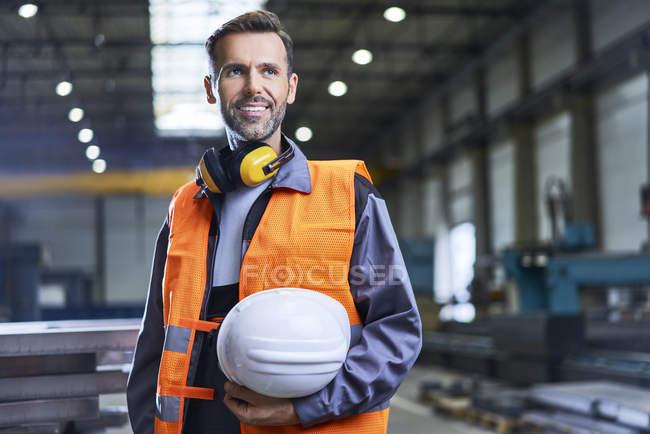 Porträt eines lächelnden Mannes in Schutzkleidung in der Fabrik — Stockfoto