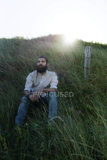 Молодой человек сидит на траве на природе и мечтает — стоковое фото