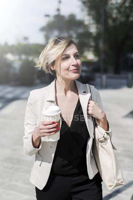 Porträt einer entspannten Geschäftsfrau mit Kaffee zum Spazierengehen — Stockfoto