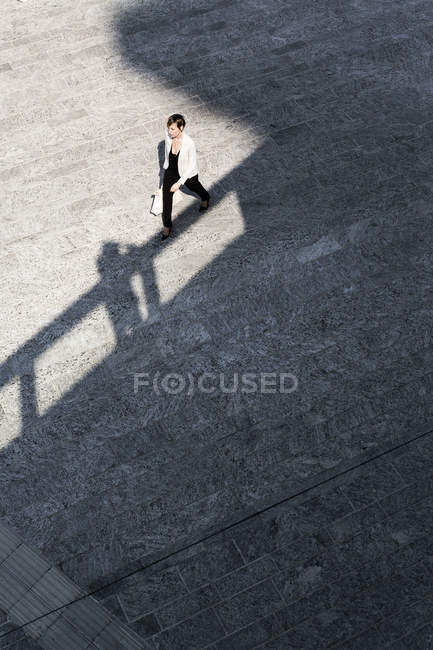 Elevated view of businesswoman crossing square in city — Stock Photo