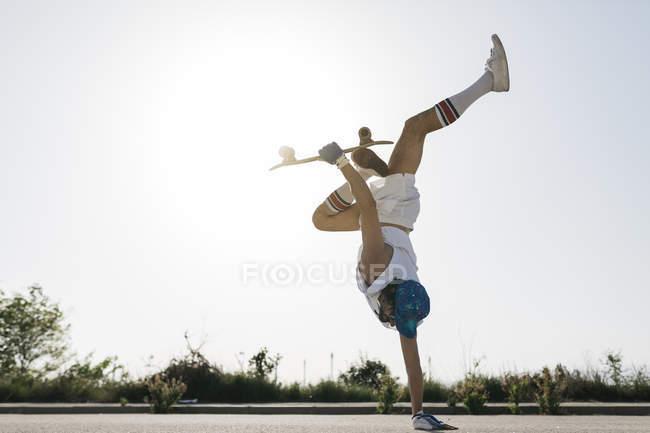 Homme sportif faisant l'astuce passionnante avec la planche à roulettes renversant sur une main sur la rue — Photo de stock