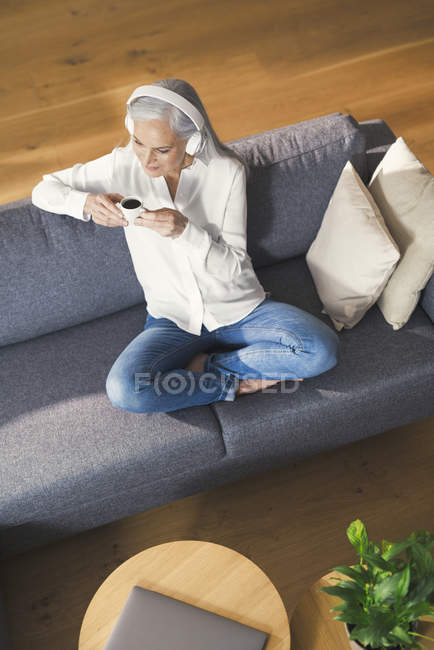 Senior woman sitting on couch, listen ning music an drinking coffee — Stock Photo