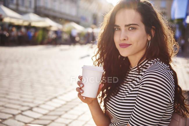 Portrait de belle jeune femme avec café à emporter dans la ville — Photo de stock