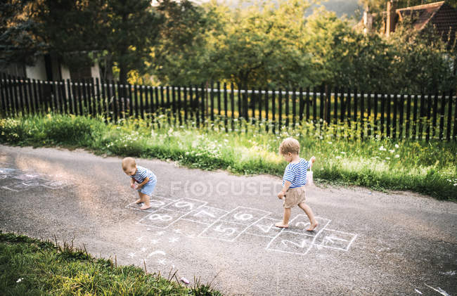 Toddler boy and little sister playing outdoors — Stock Photo